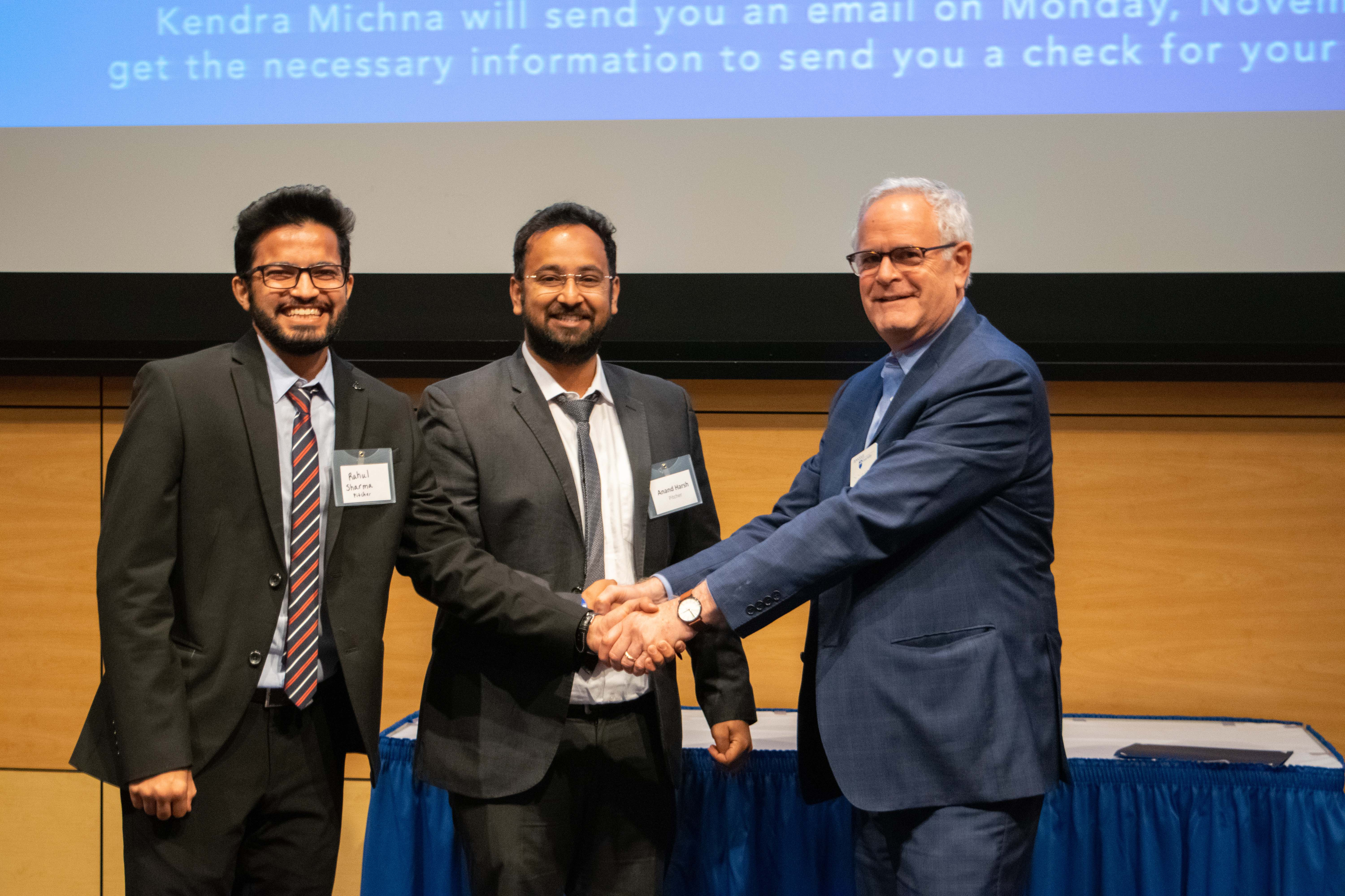 Doug Schumer presenting Rahul Sharma and Harsh Anand with their award