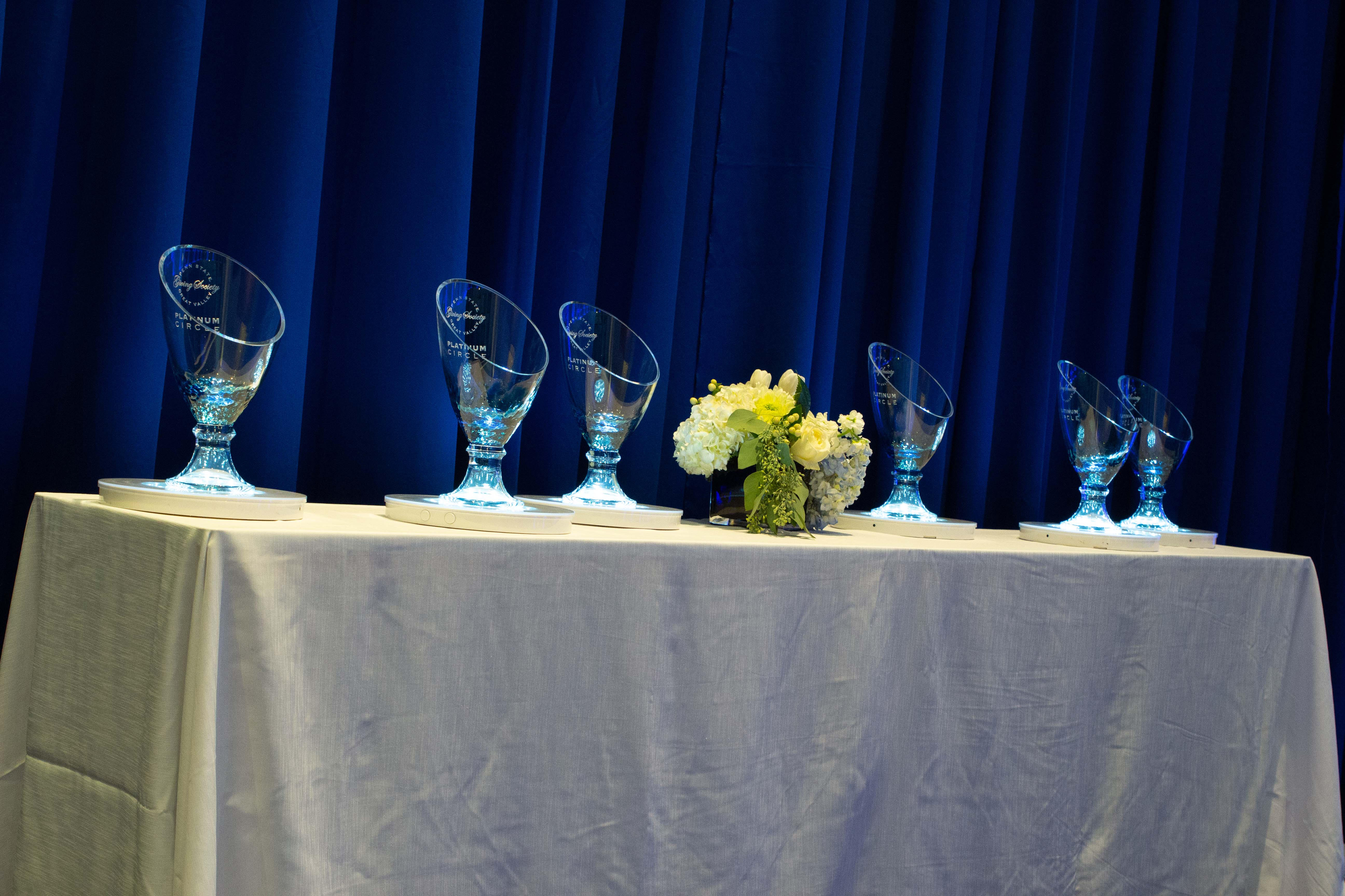 Glass vases etched with the Great Valley Giving Society logo on a table