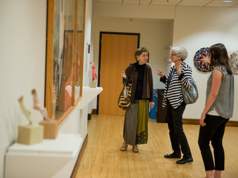 Photo of three women looking at artwork in Henry Gallery
