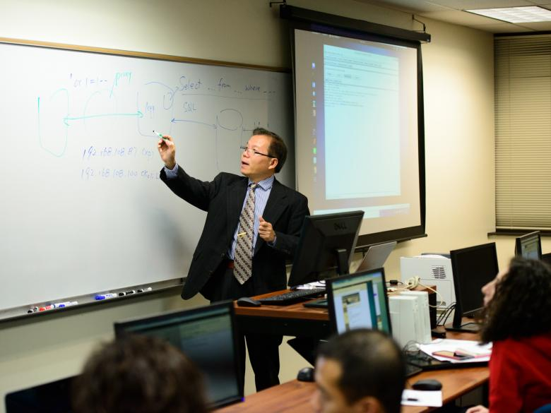 Instructor writing on whiteboard in classroom