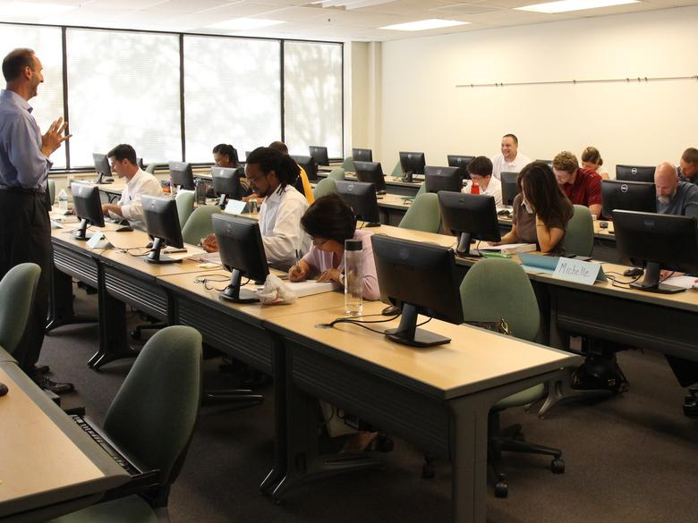 Photo of instructor talking to a students in a classroom