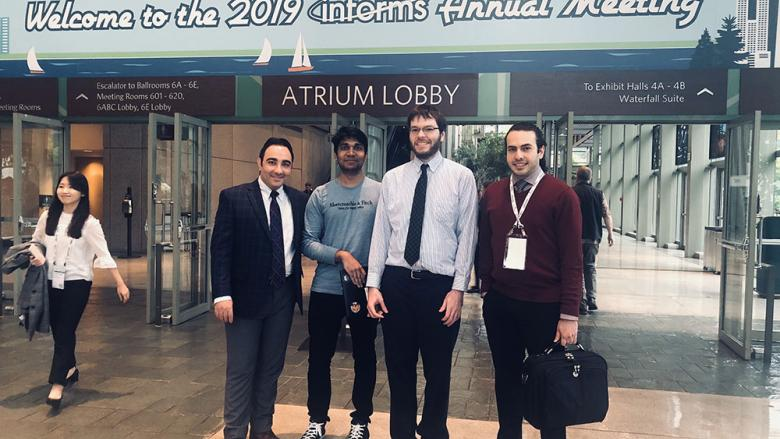Mohamad Darayi, Devendra Jaiswal, Scott Clayman and Ashkan Negahban standing in front of the INFORMS conference sign