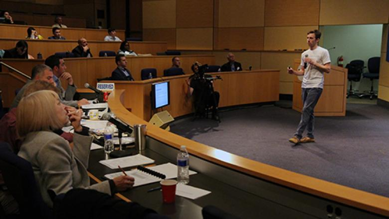 Student presenting business ideas in an auditorium to a panel of judges