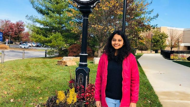 Shanmugapriya Viswanathan stands in front of the outdoor clock at Penn State Great Valley