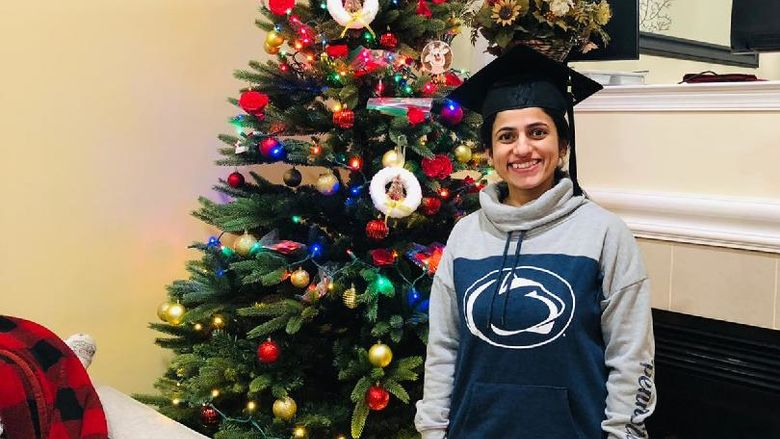 Anshul Sarvate, wearing a Penn State sweatshirt and a graduation cap, stands in front of a Christmas tree