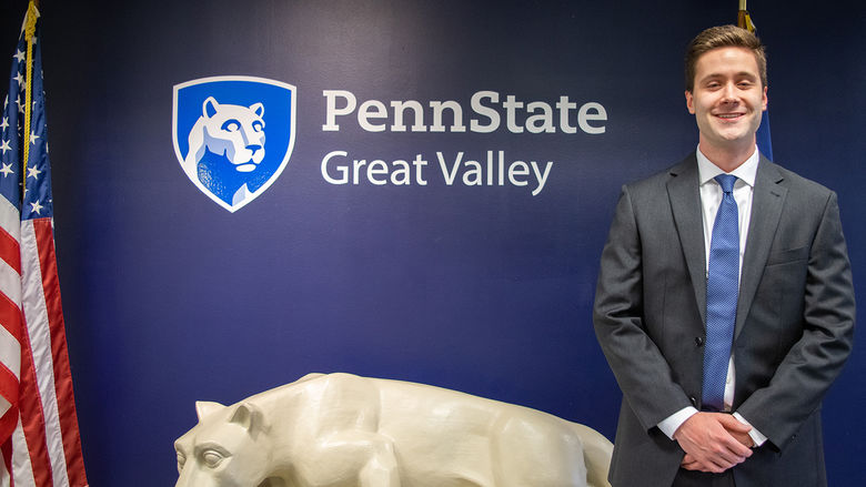 John Boland standing next to a Nittany Lion statue under the Penn State Great Valley logo