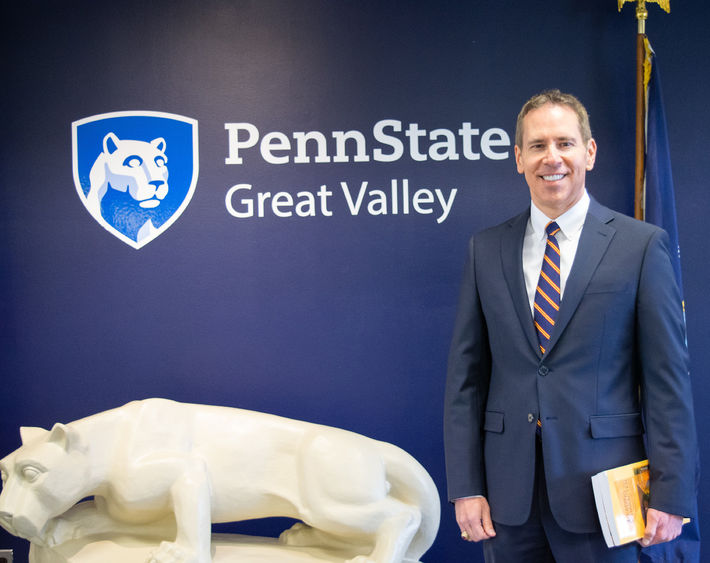 John J. Sosik standing in front of a nittany lion statue and a blue wall with the Penn State Great Valley logo