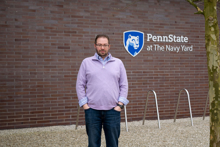 Todd Krout standing in front of the Penn State at the Navy Yard logo on Build 7R at the Navy Yard